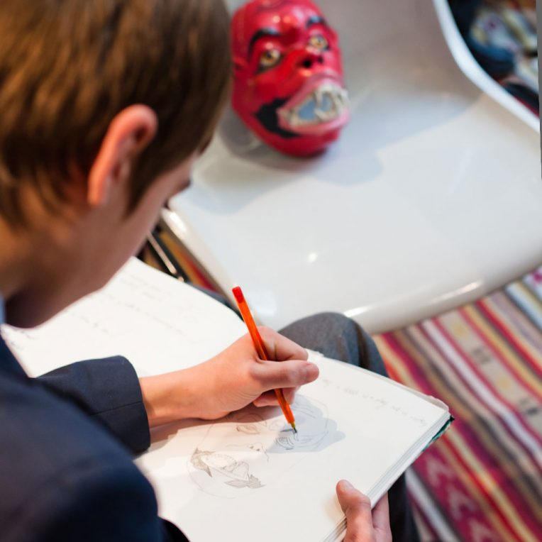 A boy in school uniform is drawing a red face mask propped up on a grey plastic chair in front of him.