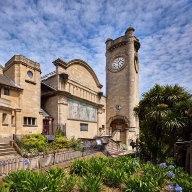 A shot of the exterior of the Horniman - a large pale yellow stone clocktower with rounded edges, a building next to it with a curved roof and a mosaic, and a third structure closer to the camera with a peaked roof, made of similar stone. There is a path along the front of all three with flower beds featuring green and purple flowers in front of the camera. The sky is blue