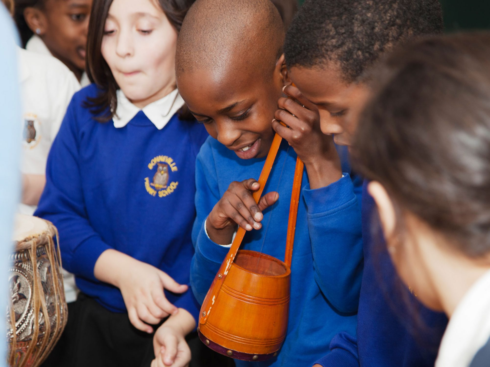 Four children are grouped around some instruments wearing blue jumpers. One child is holding a stringed drum shaped instrument and is smiling. There is a drum just seen in front of them.