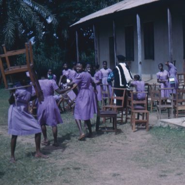 A group of school children moving chairs outside school building.