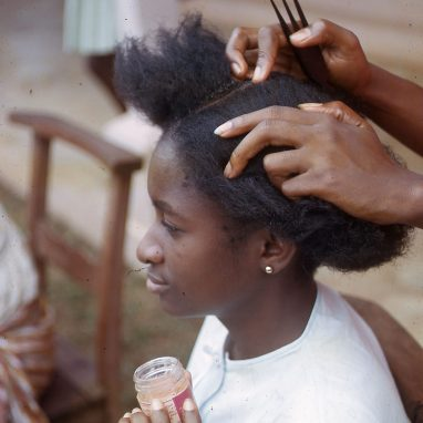 A woman is having her hair done - it has been parted by some hands (person unseen) who is also holding an afro comb. The girl wears a white top and is holding up a pot of hair product for the person doing her hair to use.