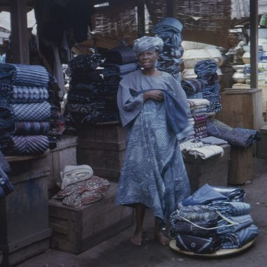 photograph of woman standing in market street/ She is wearing blue tie-dye fabric and is selling the same fabric at a shop